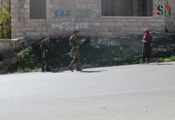 Israeli forces bag-searching a Palestinian woman