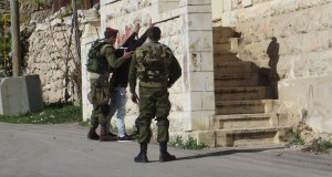 Israeli forces body-searching Palestinian man