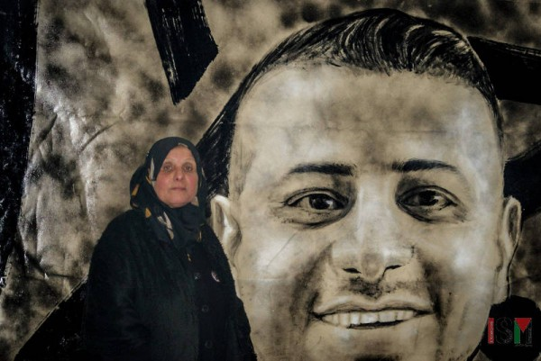 Motaz'mother in font of a poster of her son