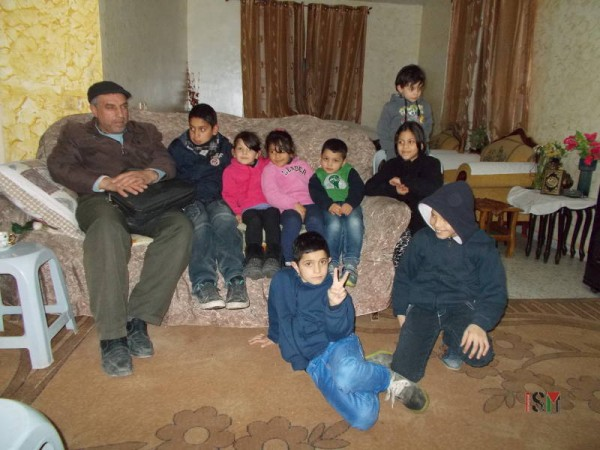 Friend Nuredin Amro and his son, Abedkarim sit on the far left side. Seven of the children who live in this house are, from left to right: Mira, Mayaan, Ahmad, Yara. On top, Fajer. On the floor, Mohammad and Badar.