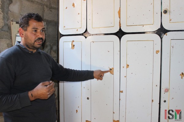 Amar points out effects of shrapnel on his cupboard