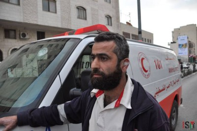 Injured ambulance driver with the broken windshield in the background.