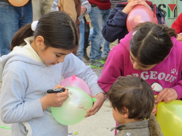 Girls writing their wishes for the future on balloons