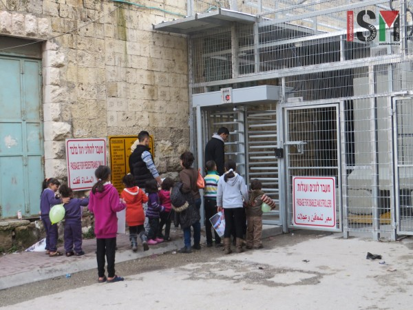 Children waiting to cross back into their 'closed military zone' neighbourhood