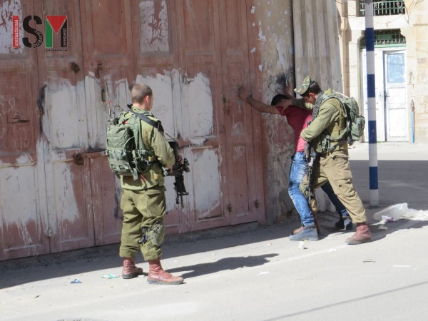 Israeli forces aggressively body-searching young Palestinian man