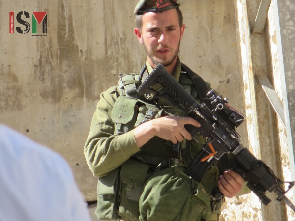 Heavily-armed Israeli soldier closely watching Palestinians pass on their way home from Prayer