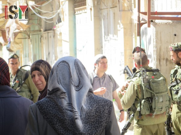 Palestinians passing by heavily-armed Israeli forces on their way home from Friday-prayer