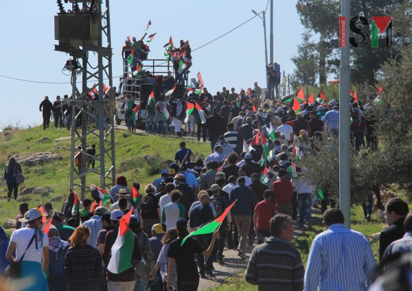 Palestinian activists marching towards the apartheid wall