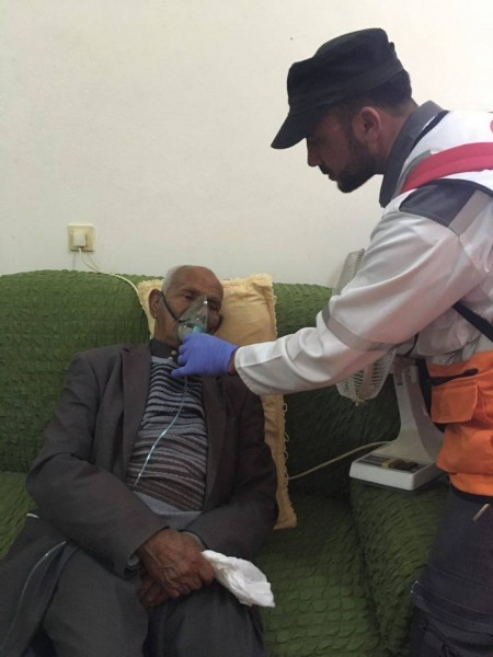 Medics treating an elderly man suffering from excessive tear gas inhalation