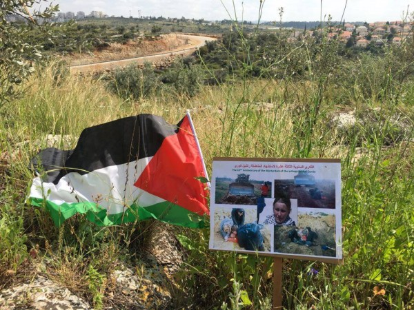 Banner commemorating Rachel Corrie next to a Palestinian flag in the fields of Ni'lin
