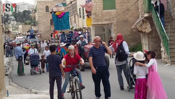 Israeli settlers celebrating while Palestinians are denied walking down the street