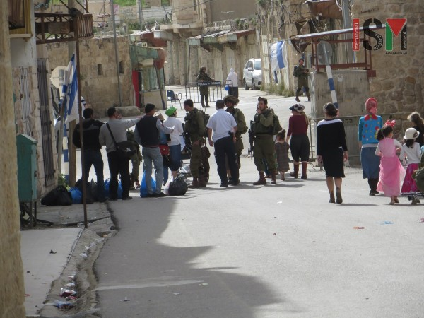Palestinian civilians stopped by Israeli forces after they opened the street for Palestinians again while settlers freely pass the checkpoint