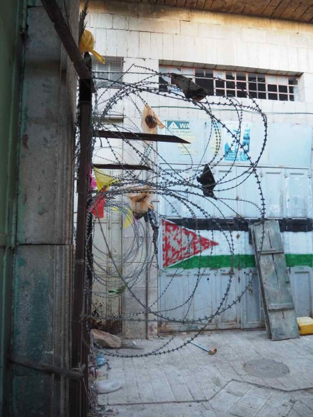 The barbed wire at the entrance to Abed's house with rubbish thrown down by settlers