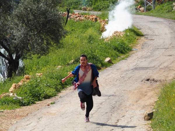 An Israeli activist runs from tear gas