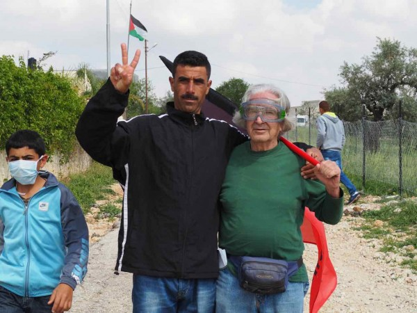 A Palestinian man and a Israeli man stand together in opposition to occupation