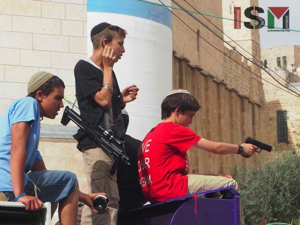 Settler children. One drinking wine, one holstering a machine gun and another aiming a pistol at onlookers
