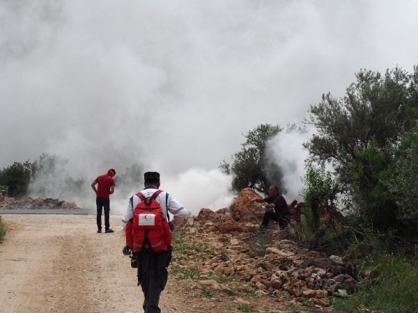 An activist and a medic amidst heavy clouds of tear gas