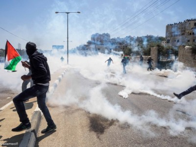 Demonstrators run from tear gas