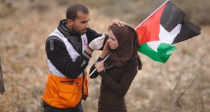A woman receives medal assistance in Nabi Saleh