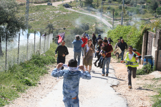 Demonstrators retreating from tear gas