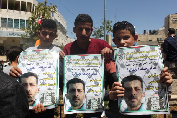 Three young demonstrators hold images of Sami