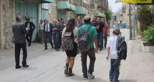The delegation on Shuhada Street, with Shuada checkpoint in the background and a group of settlers passing them