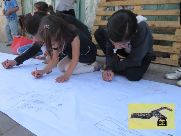 Children drawing outside Shuhada checkpoint, the 'entrance' to the closed military zone