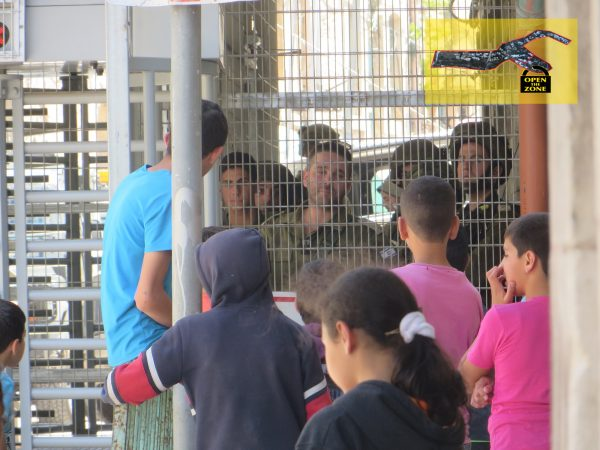 a group of children in front of Shuhada checkpoint, facing big group of soldiers