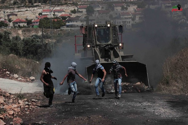 Israeli forces chasing demonstrators, illegal settlement can be seen in the back