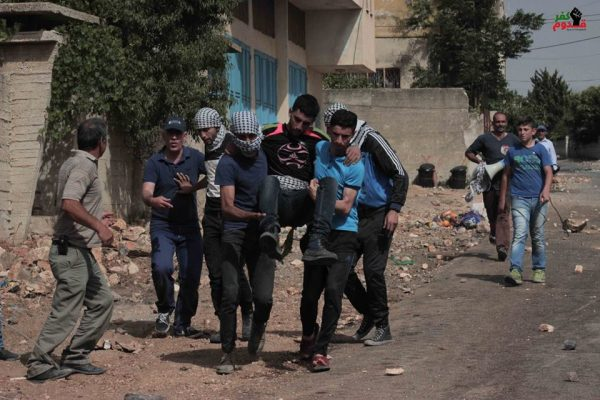 Demonstrators carrying one of the brothers to an ambulance after he was shot by Israeli forces Photo credit: Kafr Qaddum demonstration
