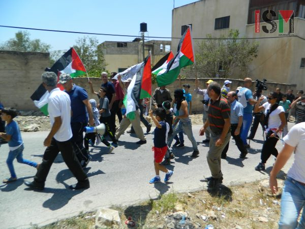 Palestinian demonstrators march towards the road