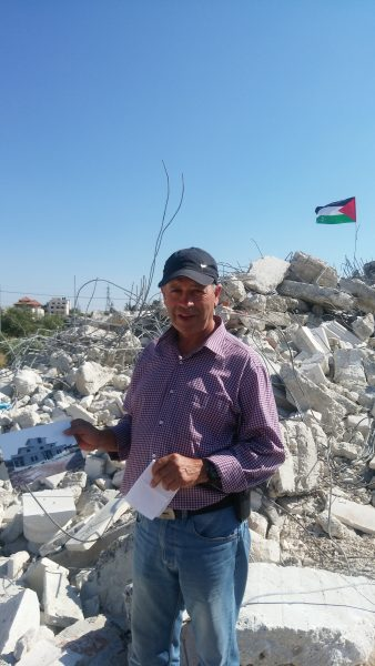Sameeh Huseen holding a picture of his home that was ruined by the Israeli army.