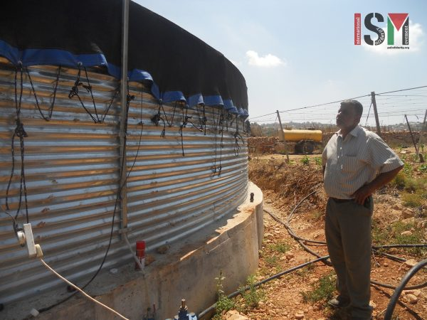 Abdullah standing at the water tank which is in the risk of getting demolished