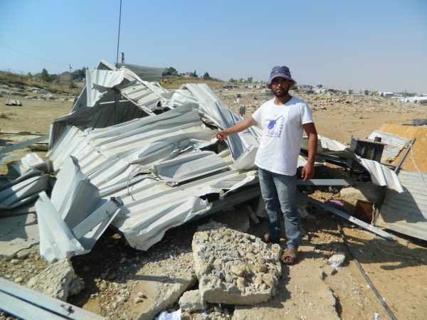 Bilal points to the ruins that used to be a home of a family until this morning, when bulldozers came and knocked it down.