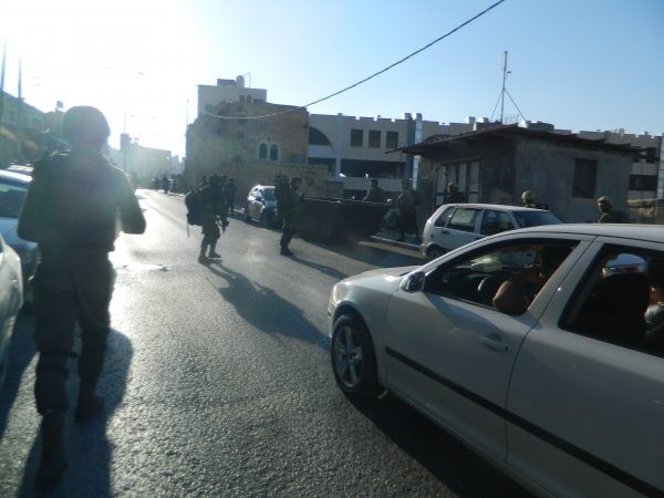 Israeli soldiers blocking traffic in H1
