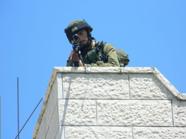 An Israeli soldier takes aim an internationals, in an effort to intimidate.