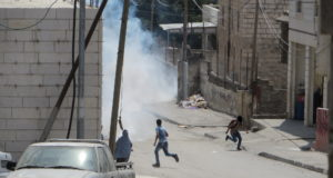 Children running away from tear gas shot by Israeli Forces at Salaymeh checkpoint