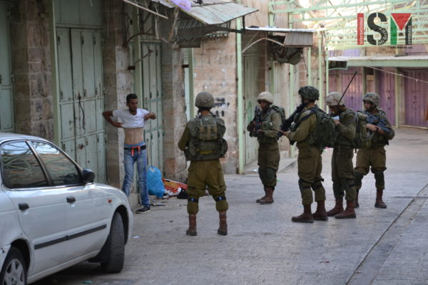 Israeli forces force Palestinian to lift up his shirt during a 'control'