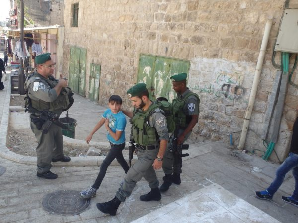 Two Palestinian boys are taken by Israeli Border Police officers to the Israeli settler boy and his father
