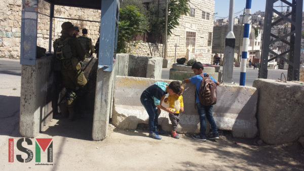 Palestinian children play outside their homes - right next to heavily armed Israeli forces watching movement of Palestinians