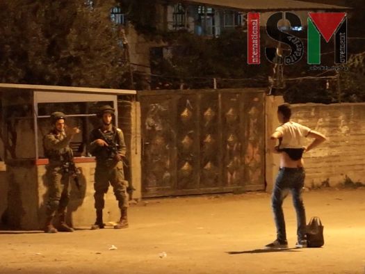 Israeli forces at night force Palestinian to lift up his shirt