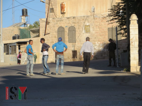 Palestinian young men are forced to lift up their shirts and trouser-legs by Israeli Forces near Ziad Jaber school