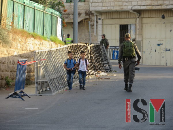 School-children forced to pass heavily-armed Israeli forces and maze of police-barriers