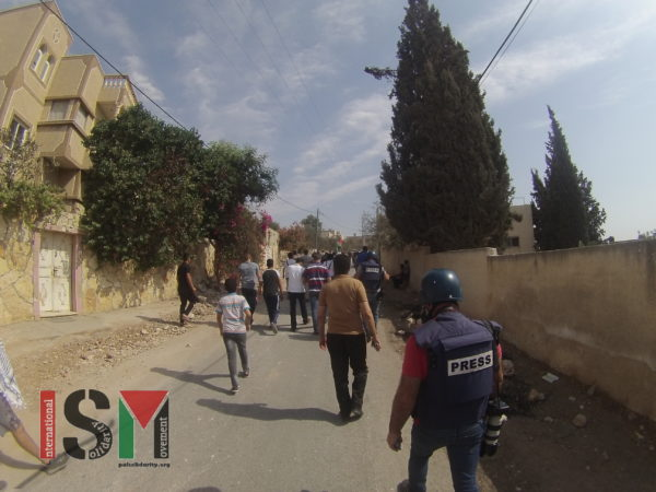 Demonstrators march in protest of road block which has been closed to Palestinians since 2003