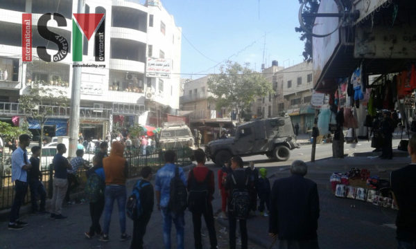 Palsetinian civilians forced to stand back as Israeli forces take over area outside Shuhada Street checkpoint.