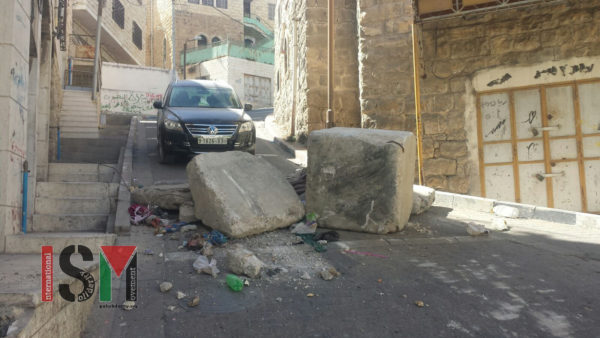 Roadblock built from large stones and rotting garbage blocking off a Palestinian side street near the Qeitun checkpoint.
