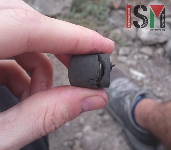 Partially ruptured rubber-coated steel bullet found in the dirt at Kafr Qaddum,