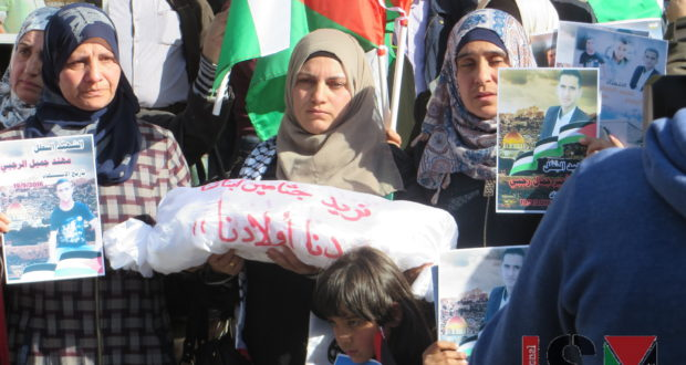 Women holding signs of their killed family members