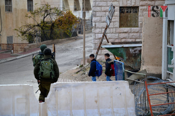 Palestinian school children passing israeli military checkpoint on their way to school