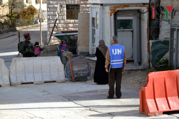 Israeli forces are detaining a Palestinian woman at the checkpoint, unaware that a member of UN delegation is present.